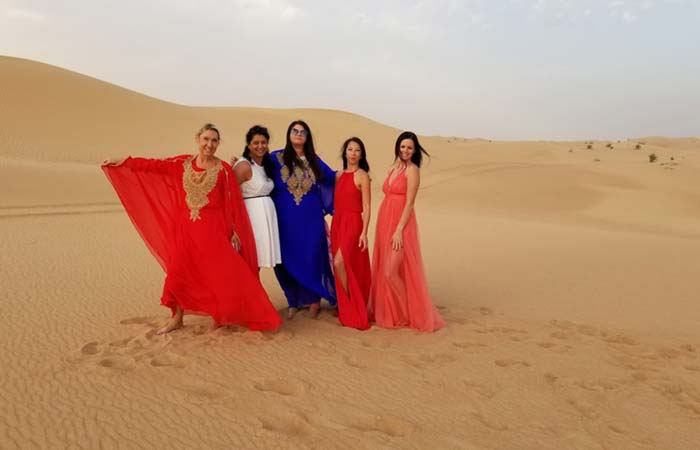Girls in tradition arabic dress posing at the desert in Dubai UAE